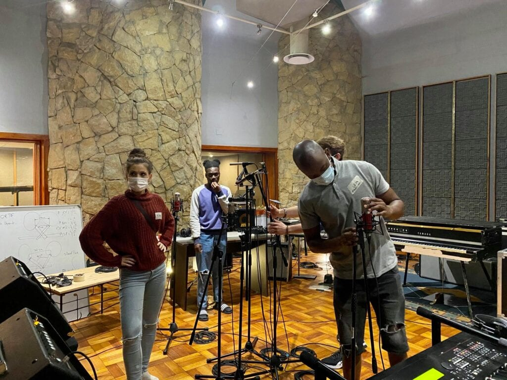 Interview Music Producer and students setting up equipment and mic stands in studio one woman and three men