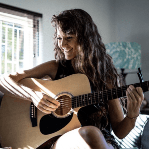Interview Music Producer Kirsten Hunneyball, student at Abbey Road Institute Johannesburg sitting on bed playing guitar, smiling with long curly hair